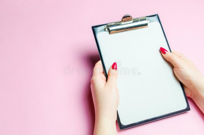 女孩拿着纪录的一种空的片剂在桃红色背景 控制和存货的概念 纪录和工作过程 免版税图库摄影