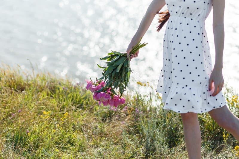 女孩拿着美丽的开花的桃红色牡丹花束  她的在风的白色礼服振翼 t美好的夏天视图  库存图片