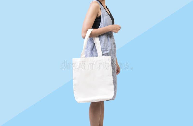 女孩拿着袋子大模型空白模板的帆布织品 库存照片
