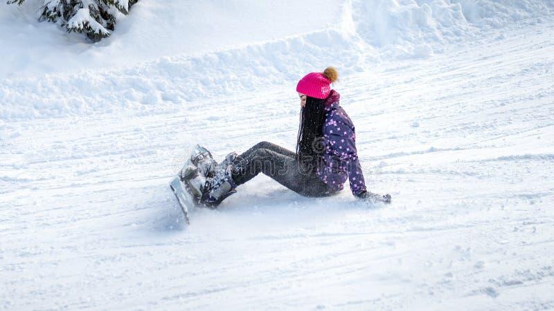女孩挡雪板跌倒了和坐雪 免版税库存照片