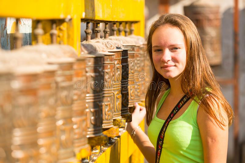 女孩接触转动的西藏佛教地藏车在Boudhanath stupa 免版税库存图片