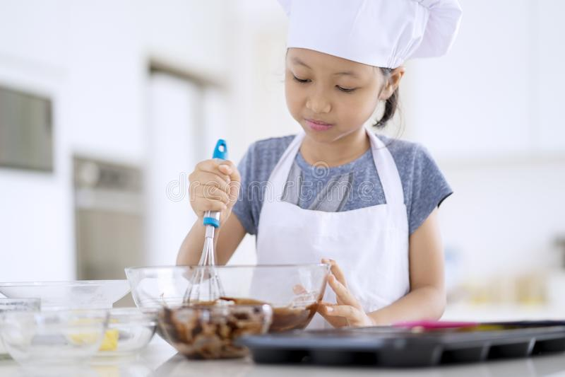 女孩搅拌在碗的曲奇饼面团 免版税库存图片