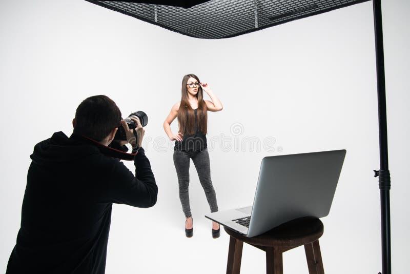 女孩摄影师为在黑色的模型照相在白色背景 免版税库存图片
