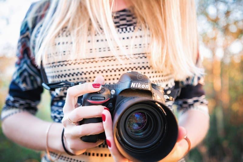 女孩摄影师举行尼康D610照相机和Nikkor 50mm f/1 4G透镜 库存图片