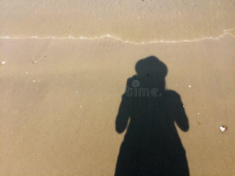 女孩摄影师在沙子的` s阴影 免版税库存图片