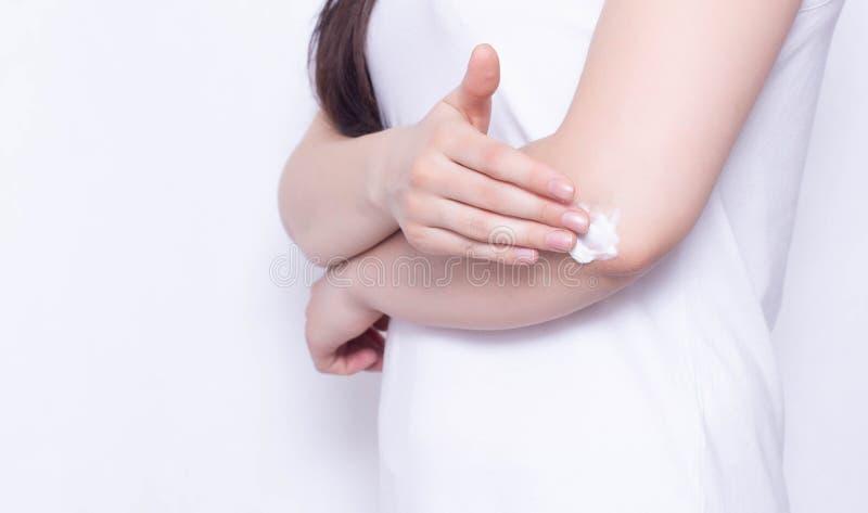 女孩摩擦医治用的奶油和香脂在肘关节解除痛苦和炎症,白色背景,拷贝空间,反 免版税库存图片