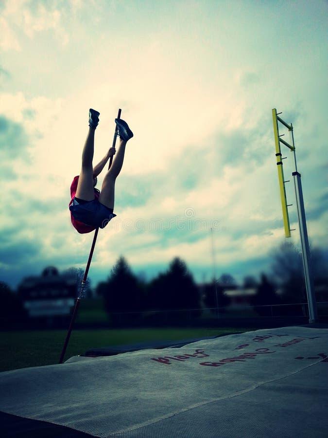 女孩撑竿跳高 图库摄影