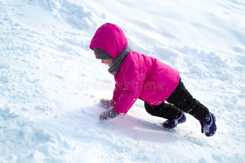 女孩攀登冰小山 库存图片