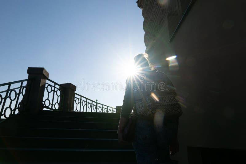 女孩攀登台阶反对太阳在早晨城市 ?? 库存图片