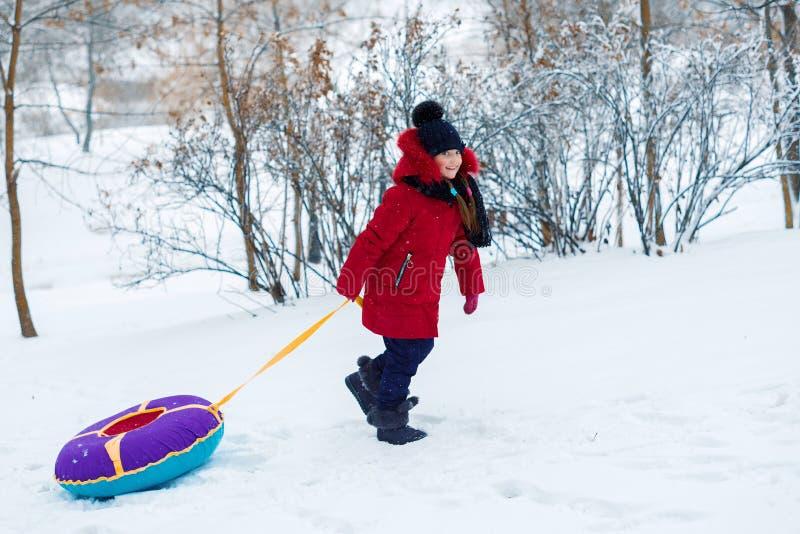 女孩攀登山 孩子拉扯雪撬 免版税库存照片