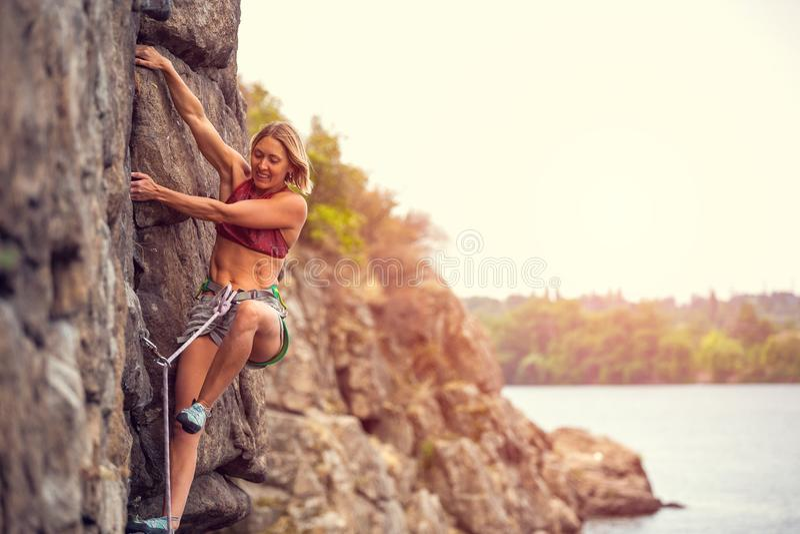 女孩攀登岩石 库存图片