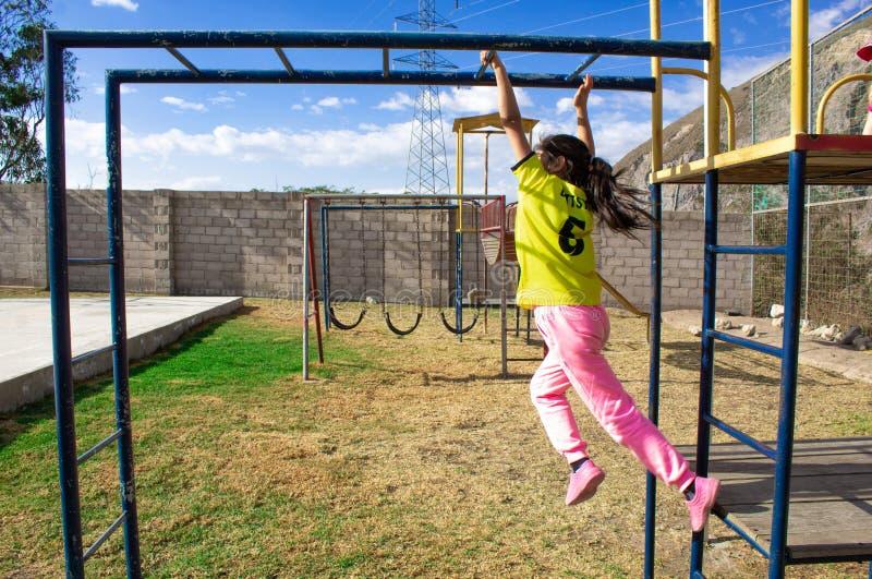 女孩攀登标志横线 在操场 免版税库存图片