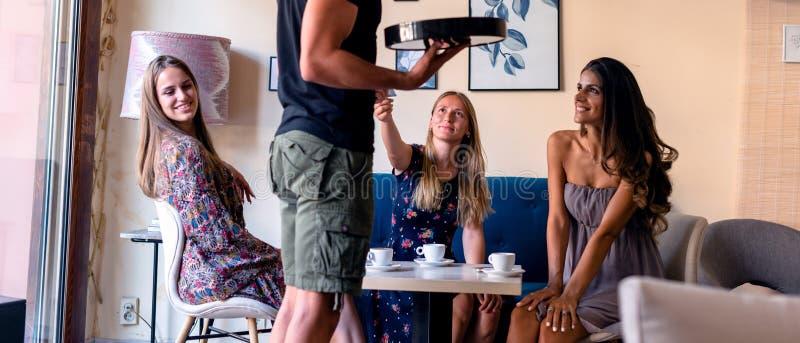 女孩支付与在咖啡馆的信用卡,而挥动与侍者的其他女孩 库存图片