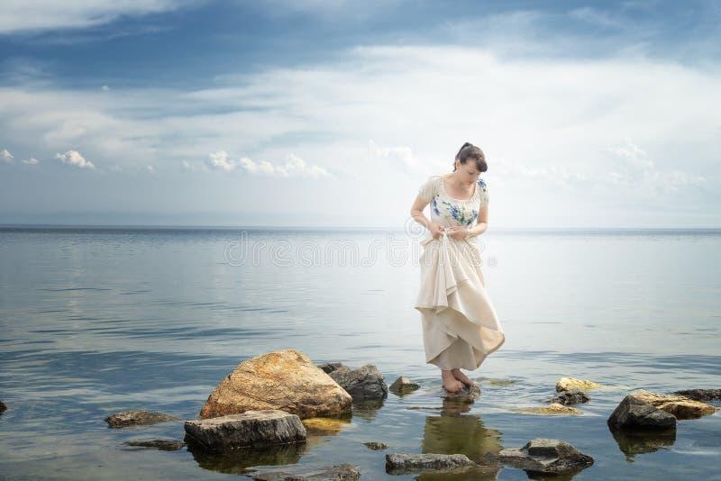 女孩支持在石头的一件礼服 贝加尔湖湖 库存照片