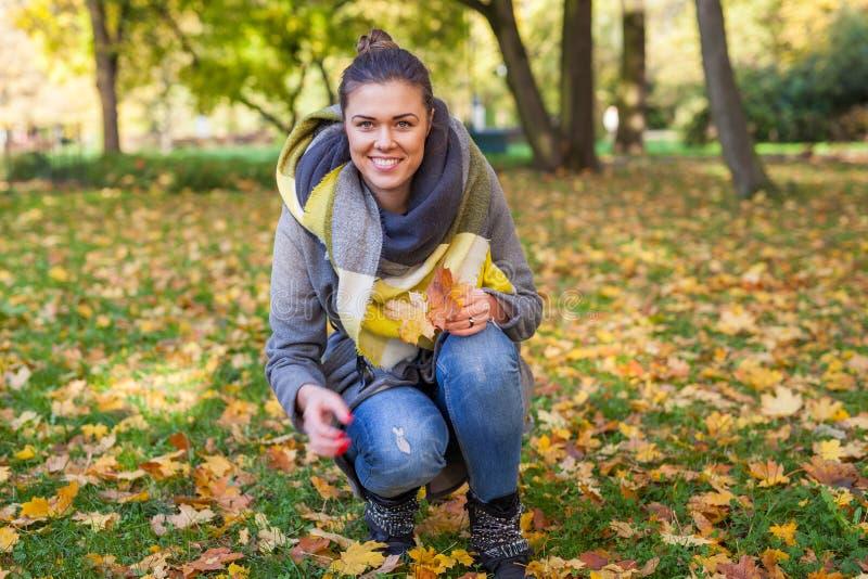 女孩收集花束的五颜六色的叶子 秋天t 库存图片