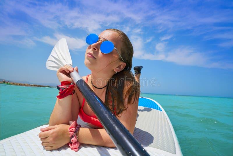 女孩放松了说谎在桨水橇板一口 免版税图库摄影
