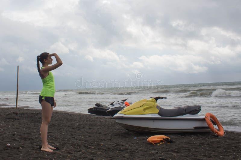 女孩救生员,有救生当班俯视的海的橙色浮体的,海洋海滩 在海滩的水滑行车 库存图片