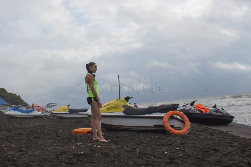 女孩救生员,有救生当班俯视的海的橙色浮体的,海洋海滩 在海滩的水滑行车 免版税库存图片