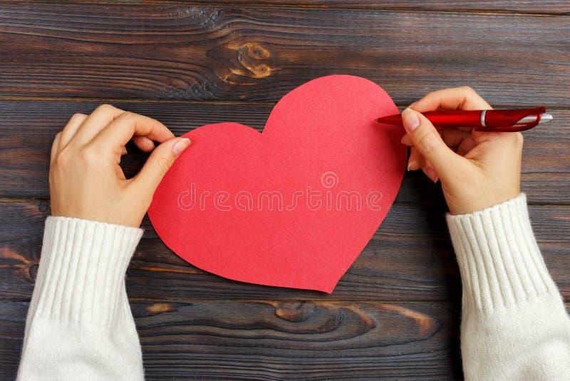 女孩文字情书的手在情人节 手工制造红色心脏明信片 妇女在明信片写为2月14日假日铈 免版税图库摄影