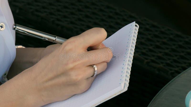 女孩文字的特写镜头在笔记本的 免版税库存照片