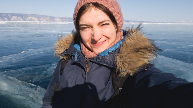 女孩旅客在冬天贝加尔湖做一selfie 冰的湖 太阳是明亮的,女孩起皱纹她的鼻子 图库摄影