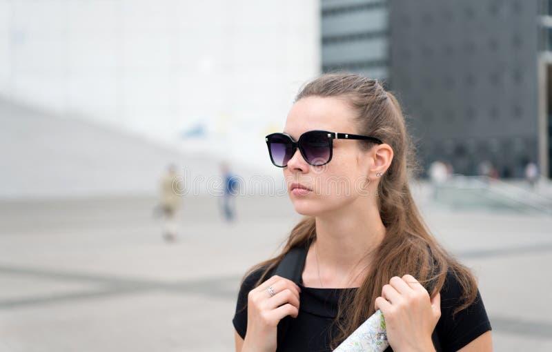 女孩旅游太阳镜享受看法巴黎广场市中心 在都市建筑学拷贝空间前面的妇女立场 必需 库存照片