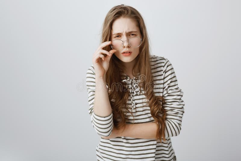 女孩明显地看不到,不用玻璃 皱眉逗人喜爱的年轻的少年斜眼看和,有坏视觉,离开 免版税库存图片