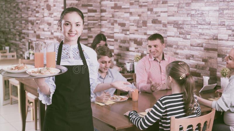 女孩是准备服务沙拉和汁液给年轻访客 免版税库存图片