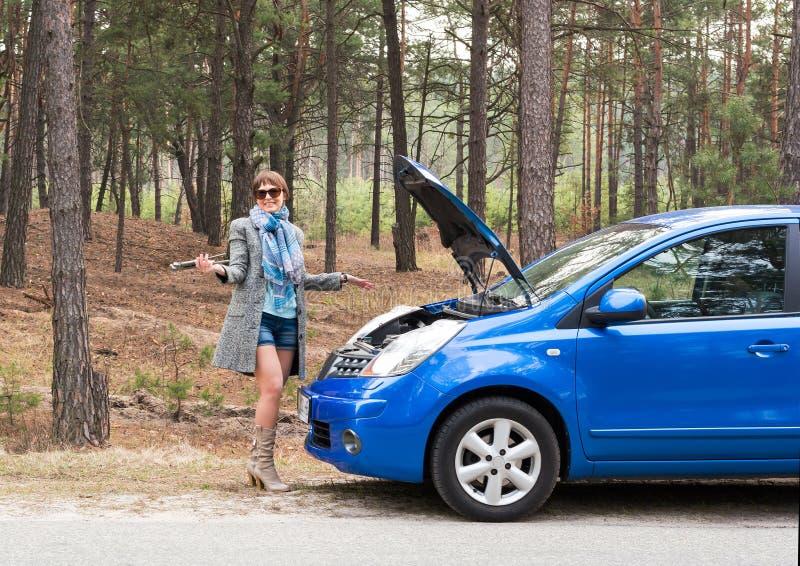 女孩是困惑不解与在开放汽车敞篷的错误板钳 图库摄影