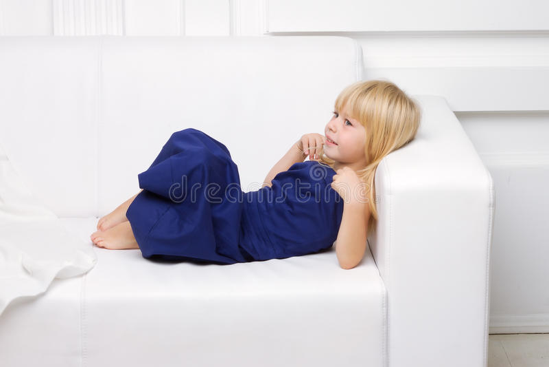 女孩是在一个空白沙发的蓝色礼服 库存照片