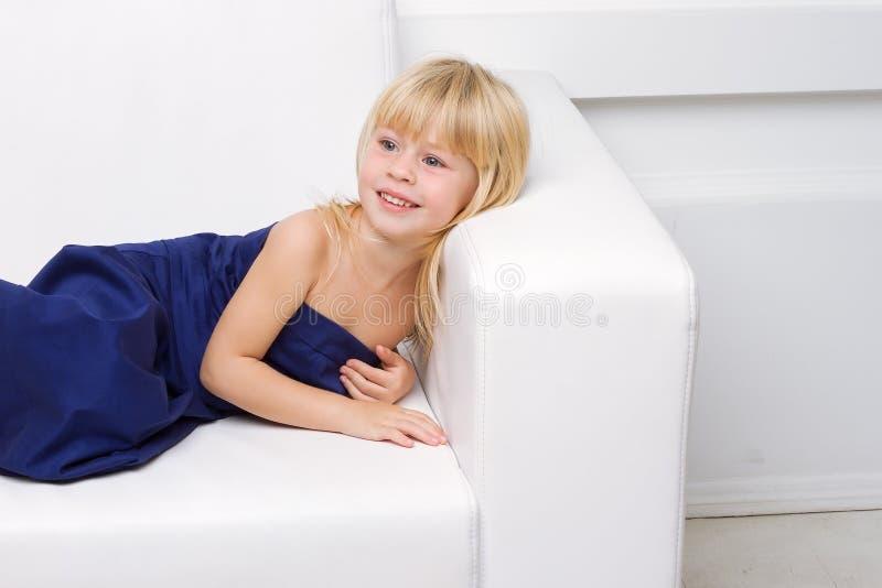 女孩是在一个空白沙发的蓝色礼服 图库摄影