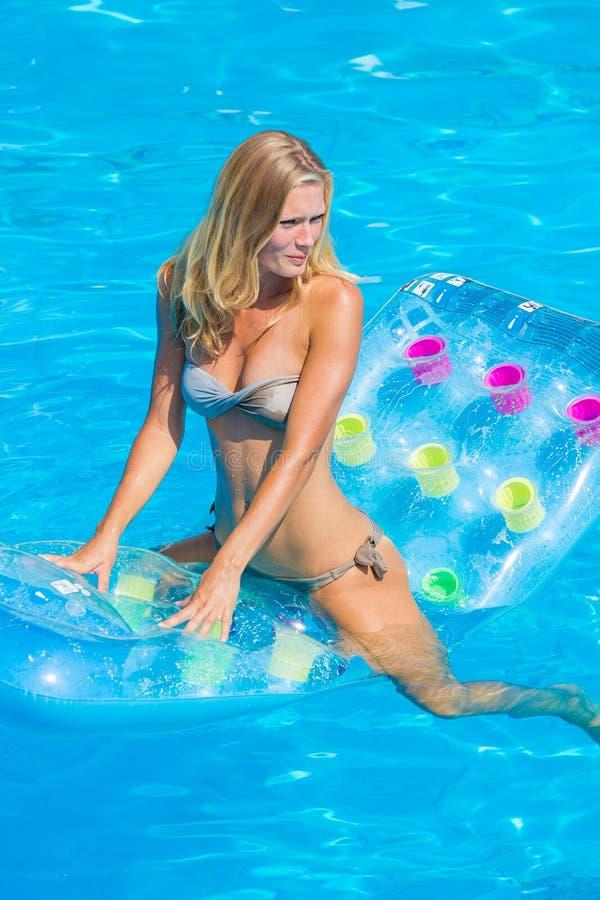 女孩是松弛在游泳池 免版税库存照片