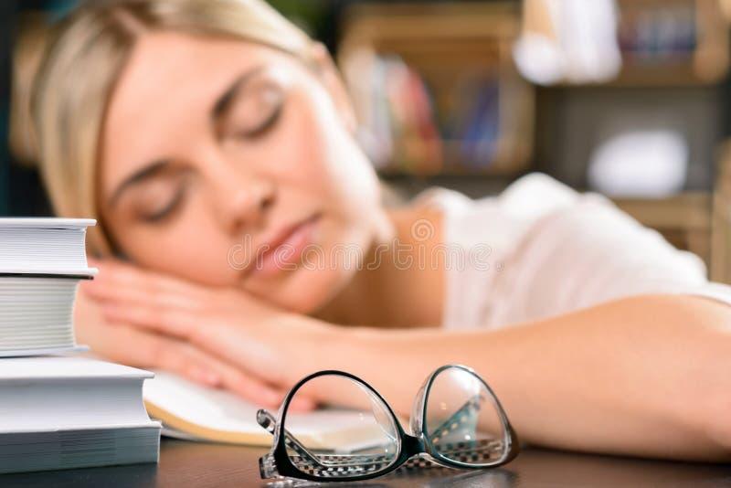 女孩是睡着在书桌上 免版税库存图片