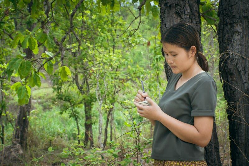 女孩是站立,采取在一个小笔记本的笔记在绿色森林里 免版税库存照片