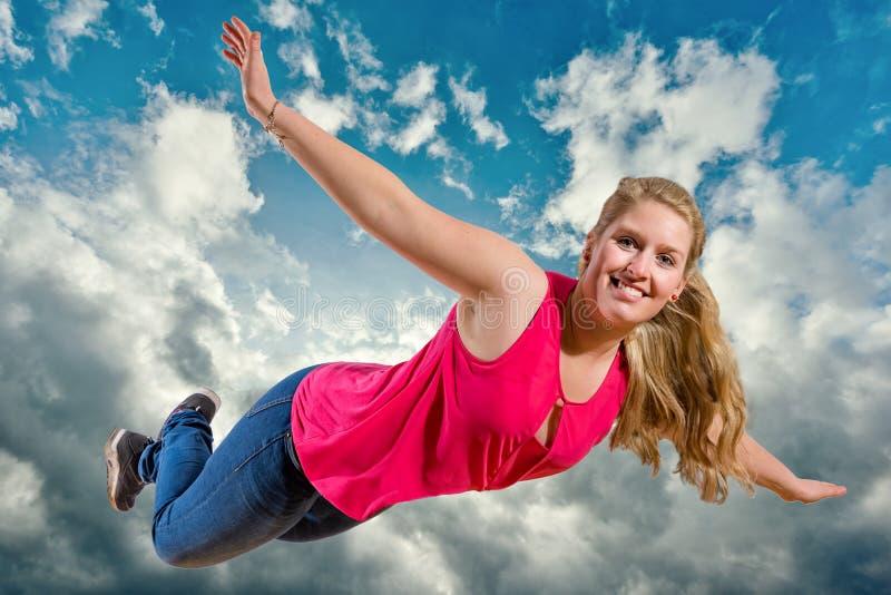 女孩是飞行和笑高在云彩 免版税库存照片