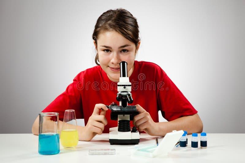 女孩显微镜使用 库存照片