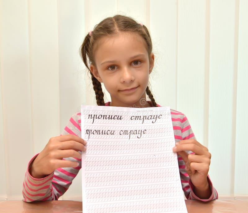 女孩显示一个书法习字簿的叶子与词的 俄国文本-习字簿,驼鸟 免版税库存照片