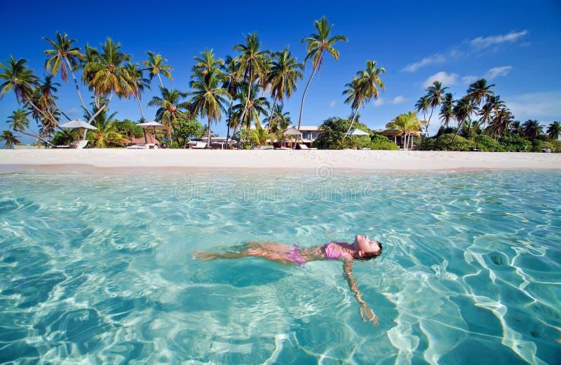 女孩晒日光浴的游泳 免版税库存图片