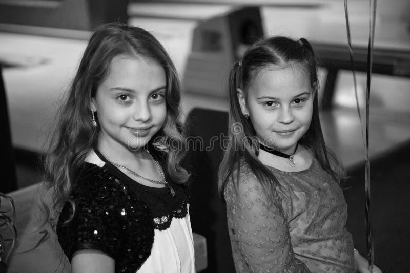 女孩最好的朋友庆祝在滚保龄球的俱乐部的生日 想法如何庆祝生日青少年 女孩逗人喜爱微笑 图库摄影
