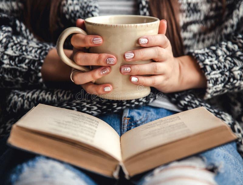 女孩有与杯子的一个断裂新鲜的咖啡在阅读书或学习以后 免版税库存照片