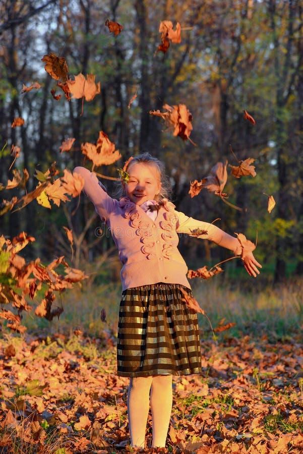 女孩有乐趣和投掷的叶子在秋天公园 免版税库存照片
