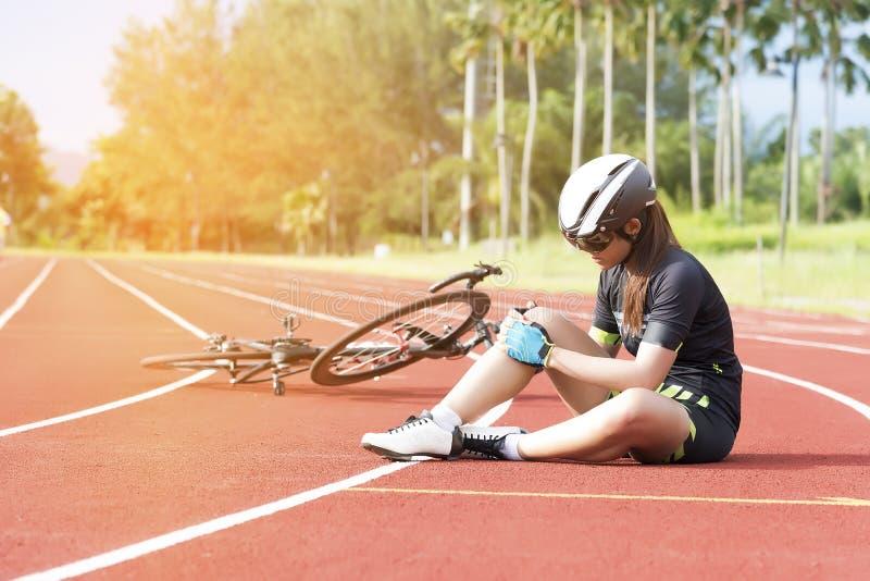 女孩有体育事故伤害在她的从自行车,体育和事故概念的膝盖 库存照片