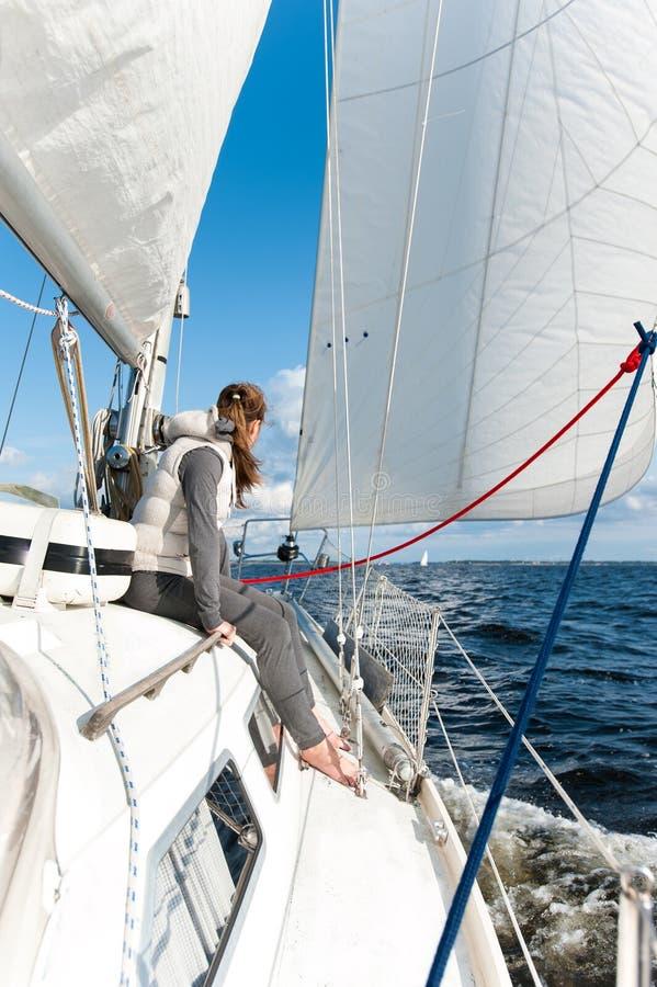女孩有在航行游艇的旅行在有风海 库存图片