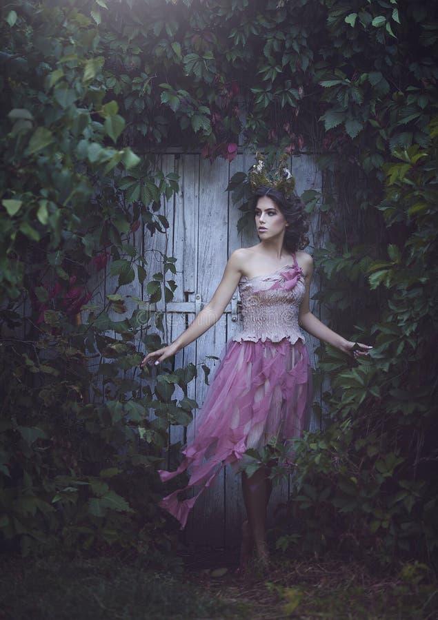 女孩有垫铁的被迷惑的公主 在破旧的衣裳的女孩神秘的神仙的生物小鹿在老门附近 万圣节 免版税库存图片