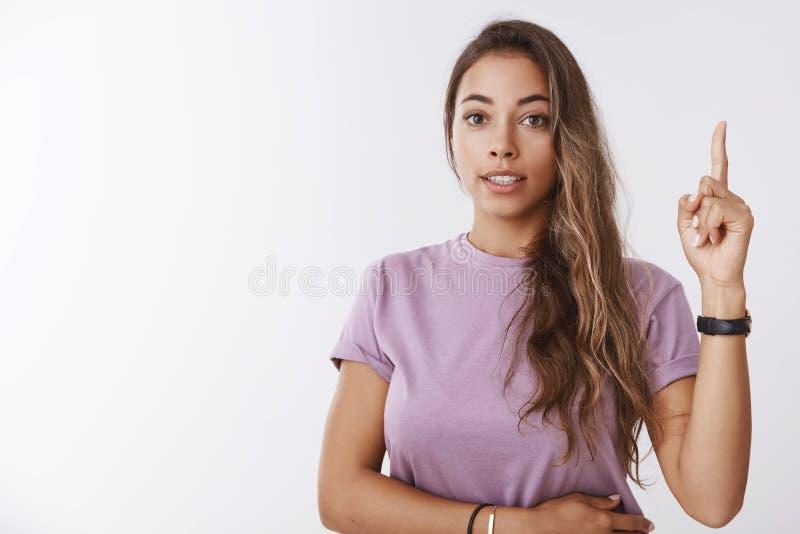 女孩有想法 提出创造性的可爱的女性的实习生提高食指尤里卡姿态的计划某事说 免版税图库摄影