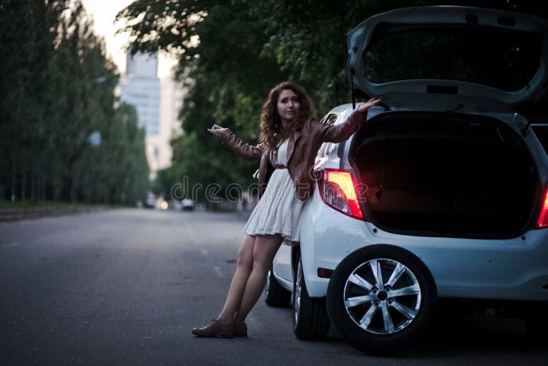 女孩有汽车,轮子替换的问题 免版税库存照片