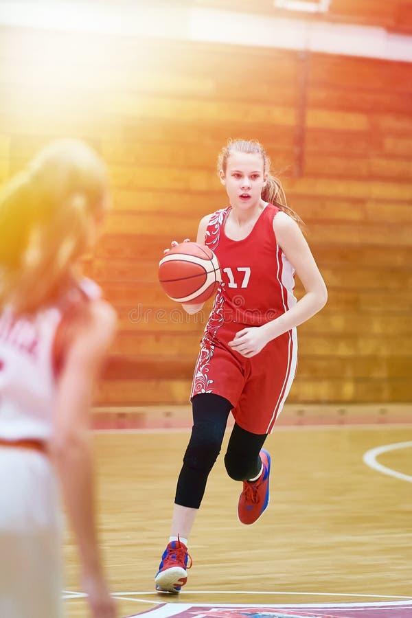 女孩有球的蓝球运动员在比赛 图库摄影