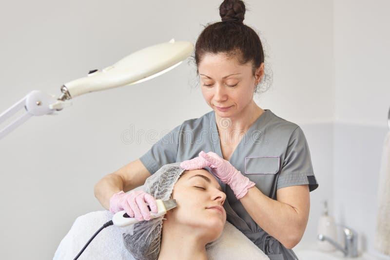 女孩有面部治疗 接受超声波在美容院的美丽的妇女气蚀削皮 皮肤洗涤的做法与 免版税图库摄影