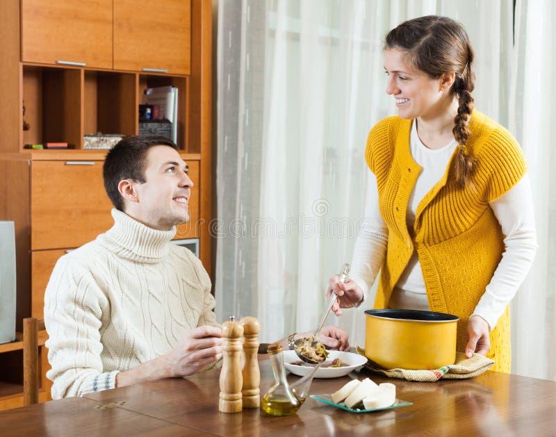 女孩服务汤在桌上 免版税图库摄影