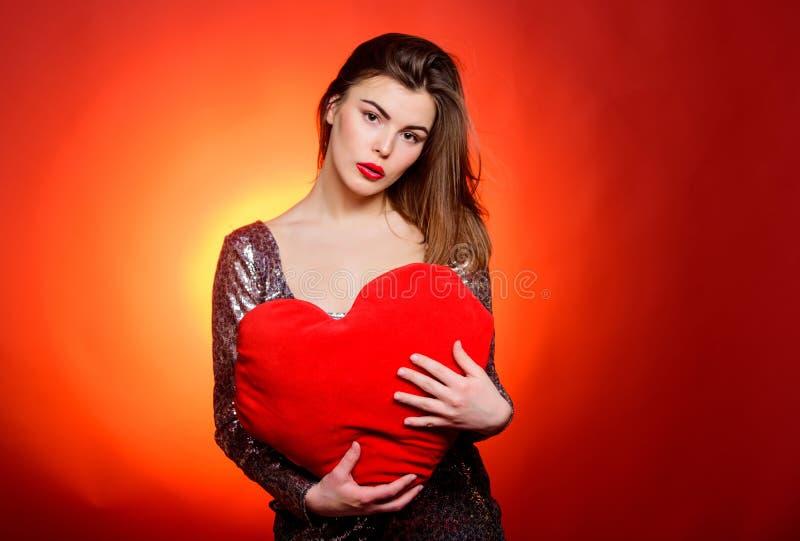 女孩构成和性感的低颈露肩的礼服 妇女有吸引力的时装模特儿举行心脏玩具华伦泰装饰 爱和 免版税库存照片